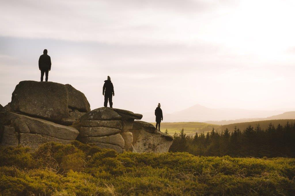 Picture of three people standing on three rocks