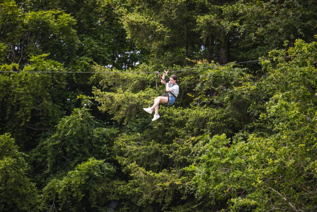 Lady descending a zipline in Coillte's farran forest park