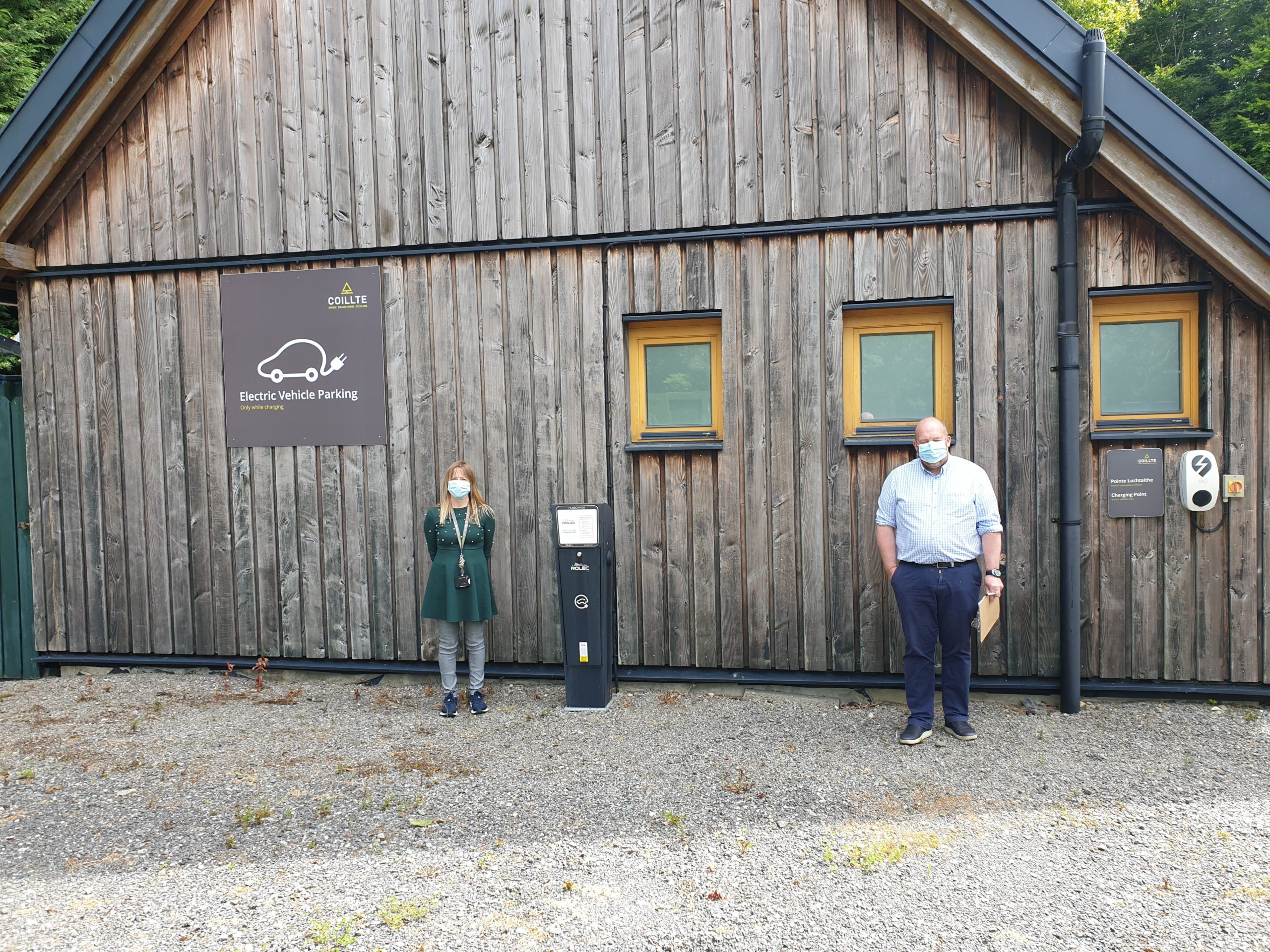 Picture of Coillte's HQ Office Manager and ISO 50001 auditor at electric car charging ports